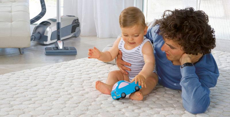 Baby und Vater im Wohnzimmer mit Staubsauger von Lux Service